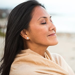 Woman relaxing on beach with hearing aids california