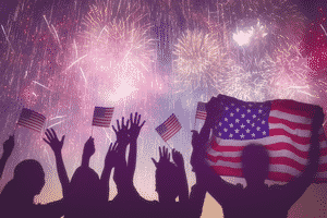 fireworks with silhouettes of people and American flags